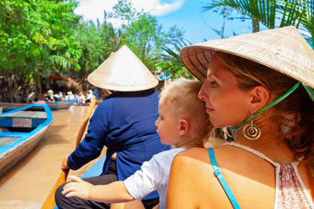 Happy family ride on traditional Vietnamese boat by yellow brown water in canal. Mekong river delta - popular travel destination for day tour during vacation in Saigon ( Ho Chi Minh ) city, Vietnam. Stock Photo