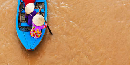 Vietnamese old woman on traditional boat paddling by yellow brown water in canal. Mekong river delta - popular travel destination for day tour during vacation in Saigon ( Ho Chi Minh ) city, Vietnam. Stock Photo