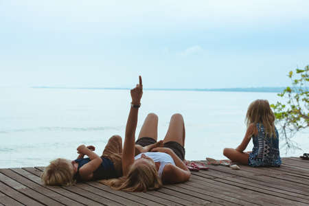 Happy mother, kids relaxing and talking on luxury hotel veranda with beautiful view. People looking at sky and blue sea. Travel lifestyle, tropical beach leisure on family summer holiday with children