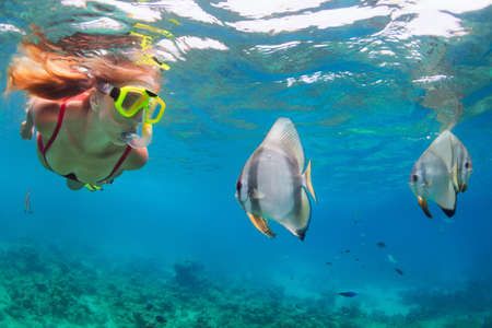 Happy family - active woman in snorkeling mask dive underwater, see tropical fishes in coral reef sea pool. Travel adventure, swimming activity and watersports on summer beach vacation with child.