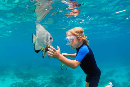 Happy family - active kid in snorkeling mask dive underwater, see tropical fish Platax ( Batfish ) in coral reef sea pool. Travel adventure, swimming activity on summer beach vacation with child.
