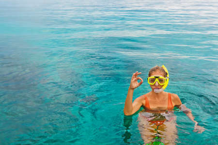 Young woman in snorkeling mask dive underwater with tropical fishes in coral reef sea pool. Show by hands divers sign OK. Travel lifestyle, water activity, beach adventure on summer holiday with child Imagens