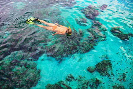 Young girl in snorkeling mask dive underwater with tropical fishes in coral reef sea pool. Travel lifestyle, water sports, outdoor adventure, swimming lessons on family summer beach holiday with kid