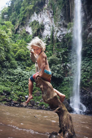 Funny happy child sit on snag under waterfall in tropical jungle canyon. Nature exploring, adventure day tour, travel activity and fun at family camp with kids on summer vacation Imagens