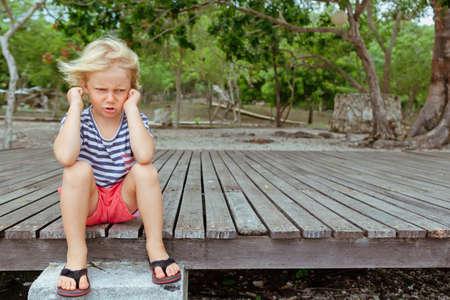 Divertido retrato de niño caucásico que parece molesto e infeliz. Concepto de niño molesto y enojado por las relaciones familiares, problemas sociales y psicología juvenil. Fondo al aire libre con espacio de copia.