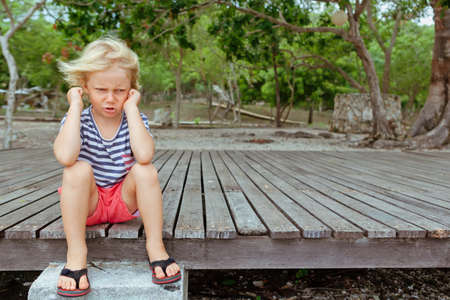 Funny portrait of caucasian kid looking annoyed and unhappy. Upset and angry child concept for family relations, social problems issues and juvenile psychology. Outdoor background with copy space.