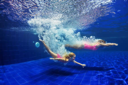 Happy family - mother, baby girl learn to swim and dive underwater. Jump with fun in swimming pool. Healthy lifestyle, active parents, people water sports activities on summer holidays with child.