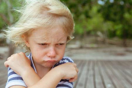 Retrato de cara de niño caucásico molesto e infeliz con los brazos cruzados. Concepto de niño molesto y enojado por las relaciones familiares, problemas sociales y psicología juvenil. Copie el fondo del espacio al aire libre.