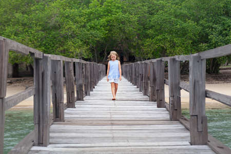 Young girl in thoughtful mood walk by wooden pier on sea sand beach in luxury resort. Popular travel destinations, active lifestyle, kids on summer family vacation.