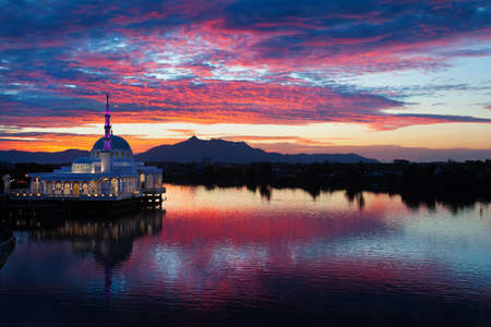 Scenic view of floating mosque on Sarawak river with colorful sunset clouds background. Waterfront landmark in Kota Kuching. Traditional culture and travel destinations on Borneo island in Malaysia.