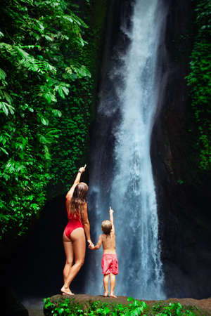 In tropical jungle happy mother with kid stand under waterfall, explore rainforest nature. Travel adventure, hiking activity with child. Lifestyle on family summer vacation and weekend walking tour.