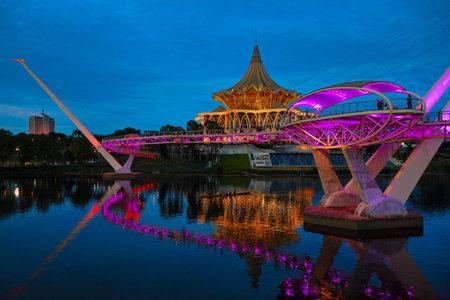 Kuching, Malaysia - March 11, 2019: Scenic night view of illuminated State Legislative Assembly and pedestrian bridge on Sarawak river. Waterfront landmark in Kota Kuching. Borneo travel destinations.
