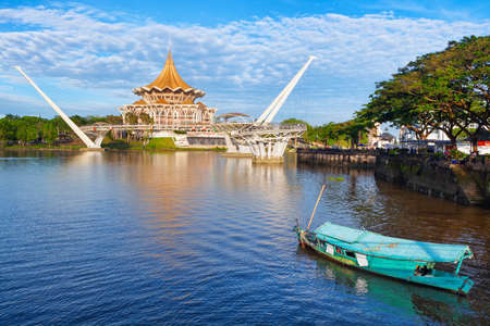 Kuching, Malaysia - March 11, 2019: Traditional boat on Sarawak river, scenic view of State Legislative Assembly, pedestrian bridge. Waterfront landmarks in Kuching city. Borneo travel destinations.