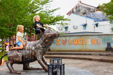 Kuching, Malaysia - March 13, 2019: Happy kids play on funny metal cat statue at waterfront of Sarawak river. Cat is a symbol of Kota Kuching