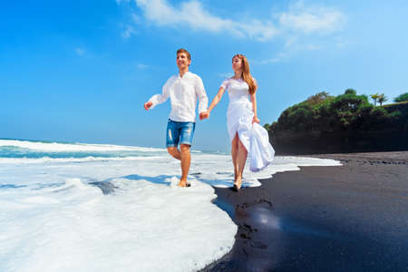 Happy family on honeymoon holiday - just married young man and woman run with fun by black sand beach along sea surf. Active lifestyle, people outdoor activity on summer vacation on tropic island.