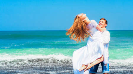 Happy family on honeymoon holiday - just married young man and woman have fun on black sand beach. Active lifestyle, people outdoor activity on summer vacation on tropical island.