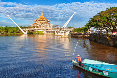 Kuching, Malaysia - March 11, 2019: Traditional boat on Sarawak river, scenic view of State Legislative Assembly, pedestrian bridge. Waterfront landmarks in Kuching city. Borneo travel destinations. Stock Photo - 122071187