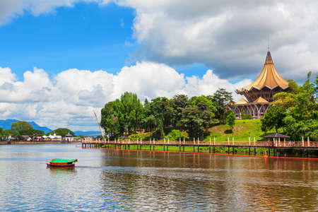 Traditional boat on Sarawak river, scenic view of State Legislative Assembly, pedestrian bridge. Waterfront landmarks in Kuching city. Borneo travel destinations.