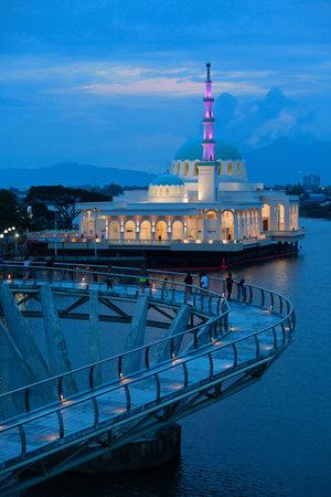 Kuching, Malaysia - March 15, 2019: Night view of illuminated floating mosque and people walking by pedestrian bridge on Sarawak river. Waterfront landmark in Kota Kuching. Borneo travel destinations.