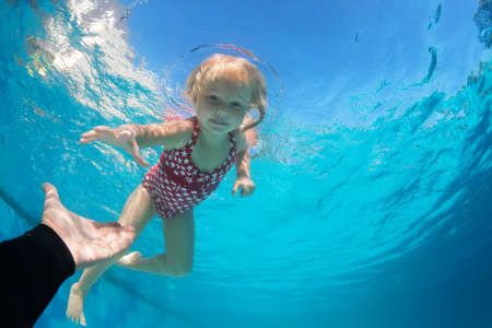 Happy family in swimming pool. Child jump deep down in pool with fun - dive underwater to reach extended hand. Healthy lifestyle, people water sport activity, swimming lessons on holidays with kids Imagens