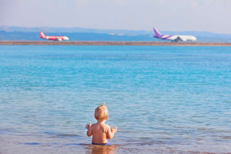 Happy kid have fun on sea beach. Child sit in water pool, watching airplanes landing at nearby airport. Travel lifestyle on family summer vacations. Popular tourist flights, tours to tropical islands