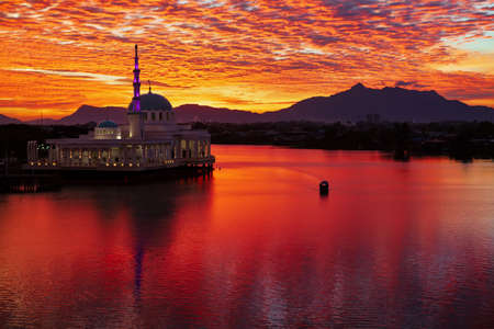Scenic view of floating mosque on Sarawak river with colorful sunset clouds background. Waterfront landmark in Kota Kuching. Traditional culture and travel destinations on Borneo island in Malaysia. Stock Photo