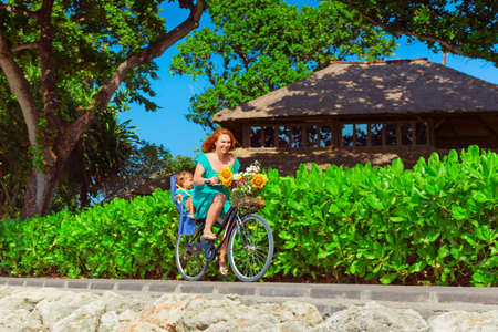 Happy family - young mother bicycling, have fun with baby daughter in child bike seat. Active parents, people outdoor activity, fitness exercises with kids on beach summer vacation in tropical islands