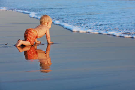 On sunset beach funny baby boy crawling by water pool to sea surf for swimming in waves. Family travel lifestyles, water outdoor activity on summer vacation with child on caribbean tropical island Foto de archivo - 121479557
