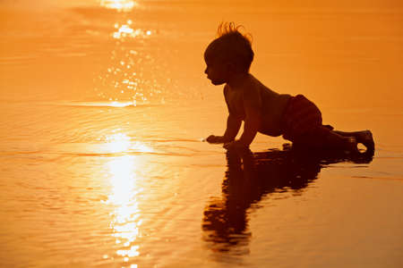 Black silhouette of funny baby boy crawling by water pool to sea surf for swimming in waves at sunset beach. Family travel lifestyles, water activity on summer vacation with kids on caribbean island Imagens