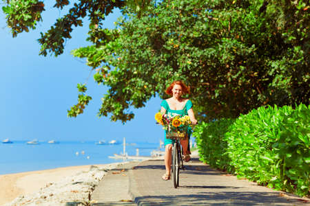 Happy family - young woman bicycling with fun. Ride by waterfront road along tropical sea beach. Active parents, people outdoor activity, fitness exercises on beach summer vacation in tropical islands