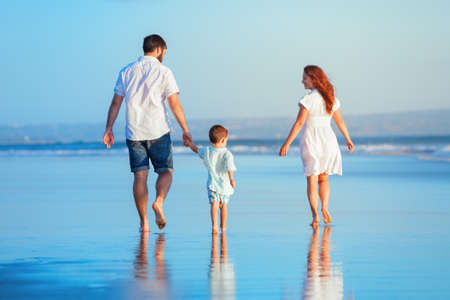 Happy family - young father, mother, baby son strolling together, child run with fun by water pool along sunset sea surf on tropical beach. Travel lifestyle, people walking with kid on summer vacation Imagens