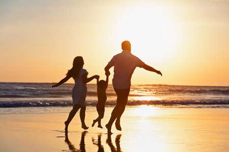 Siluetta nera della famiglia felice su priorità bassa del sole. Padre, madre, figlio piccolo corrono. Il bambino salta con divertimento in piscina lungo la spuma del mare sulla spiaggia. Stile di vita di viaggio, genitori che camminano con il bambino durante le vacanze estive.