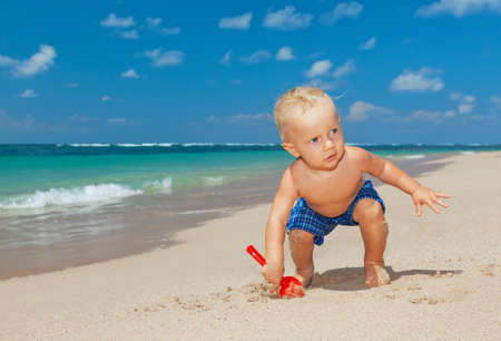 On sunny beach muddy happy baby boy play with fun, digging white sand before swimming in sea. Active children lifestyle, summer vacation travel with little kids at family resort on tropical islands.