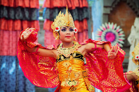 Denpasar, Bali island, Indonesia - July 11, 2015: Portrait of beautiful young Balinese woman in ethnic dancer costume, dancing traditional temple dance at art and culture festival parade. Editorial