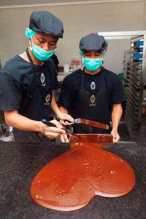 Bali island, Indonesia - October 03, 2015: Young men working at chocolate factory,  checking molten liquid raw chocolate paste consisting of hot raw cocoa mass and cocoa butter.