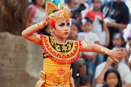 Denpasar, Bali island, Indonesia - July 11, 2015: Portrait of beautiful young Balinese woman in ethnic dancer costume, dancing traditional temple dance at art and culture festival parade. Stock Photo - 122071913