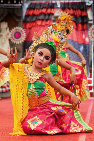 Denpasar, Bali island, Indonesia - July 11, 2015: Portrait of beautiful young Balinese women in ethnic dancer costumes, dancing traditional temple dance at art and culture festival parade.