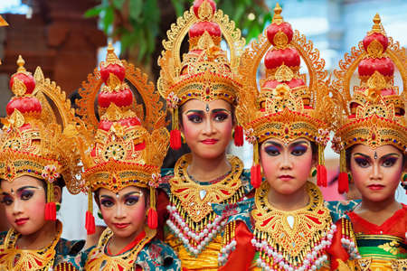 Denpasar, Bali island, Indonesia - July 11, 2015: Portrait of beautiful young Balinese women in ethnic dancer costumes, dancing traditional temple dance at art and culture festival parade. Stockfoto - 122071916
