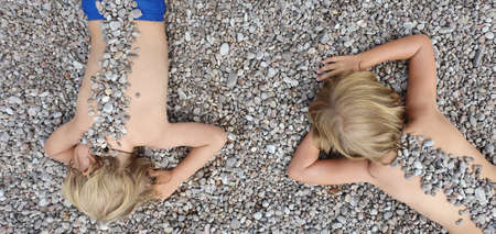 On sunny beach happy kids have fun, lying down on hot pebble, sunbathing, warming after swimming in sea. Active children lifestyle, summer vacation travel with kids on tropical family resort.