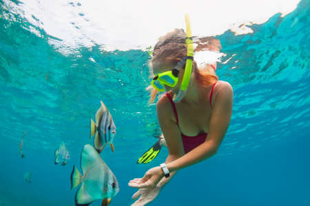Happy family - girl in snorkeling mask dive underwater, explore tropical fishes Platax ( Batfish). Travel lifestyle, beach adventure, swimming activity, water sport on summer beach holidays with kids. Stok Fotoğraf