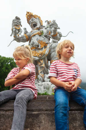 Funny little kids in botanical garden on background of ancient statue of fighting Kumbakarna from epic Hindu legend Ramayana. Traditional arts, culture of Bali, popular travel destination in Indonesia