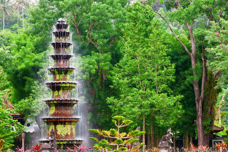 Cascade fountain in ancient water palace and tropical park Tirta Gangga with natural pools, fish ponds with statues. Culture, traditional arts of Bali island, popular travel destination in Indonesia.
