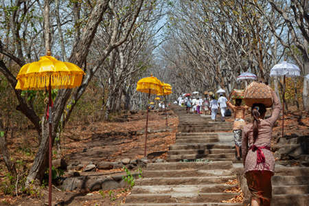 Group of women and families in traditional Balinese costumes carry religious offering to village temple for hindu ceremony. Religion, art and culture of Indonesia. Bali travel background.