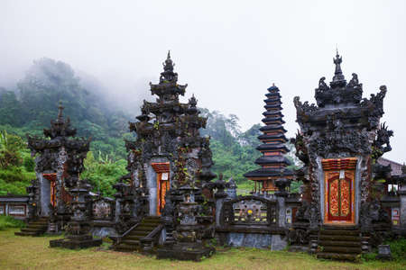 Foggy morning scenic view of ancient Balinese hindu temple at Buyan lake in mountain rainforest near Bedugul. Popular travel destinations, traditional art, culture, religion of Bali island, Indonesia.