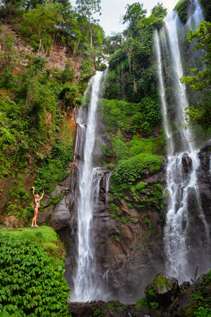 Young woman travel in Bali rainforest. Happy girl enjoy jungle nature. Stand in natural pool under Sekumpul waterfall, see on falling water. Walking tour, hiking activity adventure on family holiday.