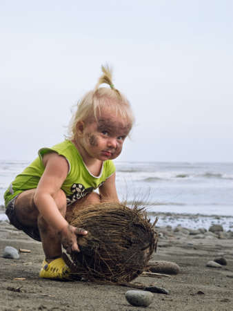 Funny portrait of smiling child with dirty face and hands playing with coconut. Having fun on black sand sea beach. Family travel lifestyle, activity on summer vacation with baby on tropical island. Stock Photo - 131121812