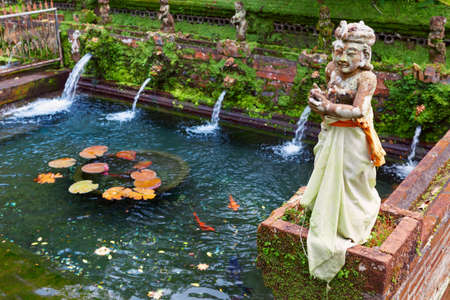 Gunung Kawi Sebatu hindu temple with holy water natural spring, pools with fish and statues in traditional costumes. Culture, arts of Bali, popular travel destination in Tegalalang, Gianyar, Indonesia