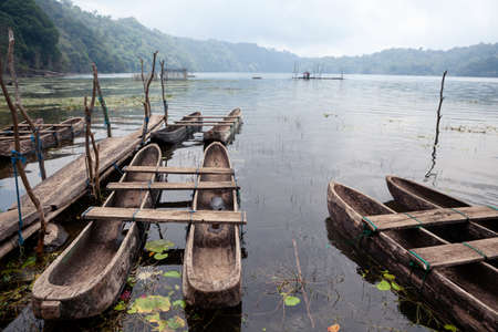 Foggy morning scenic view of traditional fisher boats on Danau Tamblingan lake, popular tourist place in tropical mountain rainforest. Travel destinations, culture, nature of Bali island, Indonesia.