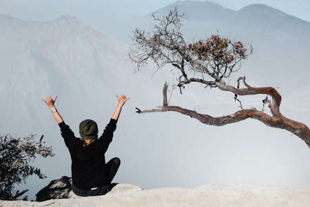 Happy young woman sit on rock above volcano Kawah Ijen crater. Look at largest in world acid lake, sulphur mine. Popular travel destination, adventure hike on family vacation in Bali, Java, Indonesia