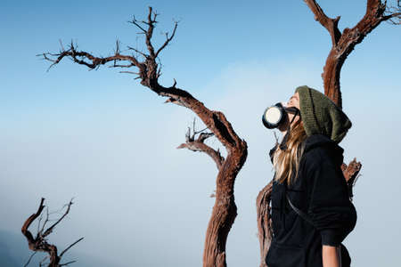 Young woman in breath filter mask to protect from toxic gas and poisonous fumes during adventure hike to active volcano Kawah Ijen with crater acid lake. Popular travel destination in Java, Indonesia